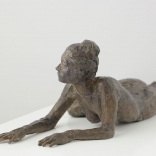 Female sculpture lying on her front side, whilst bent towards an angles, as seen in a AK Asimis Kolaitou art gallery in Santorini, Greece.