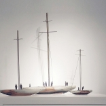 Three model boats, of different sizes with long bronze masts and clay base, produced by contemporary Greek artist Eleni Kolaitou of the Greek art gallery Asimis