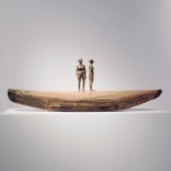 Two figurine sculptures standing on a clay boat as seen in the Greek art gallery, Asimis in Santorini