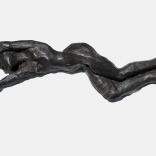 A lying bronze sculpture with hands thrown over the top, sculpted by Greek contemporary artist, Eleni Kolaitou of the Greek art gallery, AK Santorini,Greece